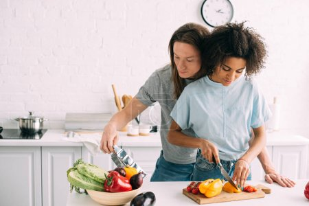 Photo for Young woman cutting bell pepper and boyfriend looking at grater at kitchen - Royalty Free Image