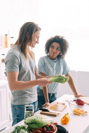Photo for Multiethnic young couple standing at kitchen with salad leaves - Royalty Free Image