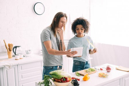 Photo for Multicultural young couple looking at recipe on digital tablet and cooking at kitchen - Royalty Free Image