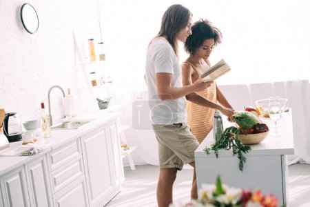 side view of young multiethnic couple cooking and looking at recipe in book