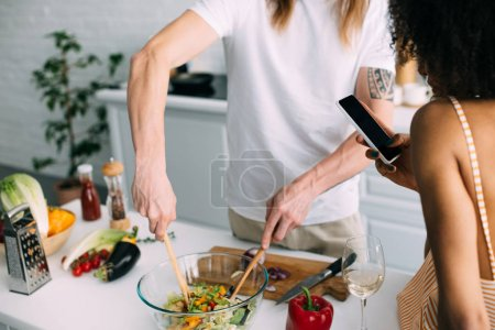 Photo for Cropped image of man cooking salad while his girlfriend shooting on smartphone at kitchen - Royalty Free Image