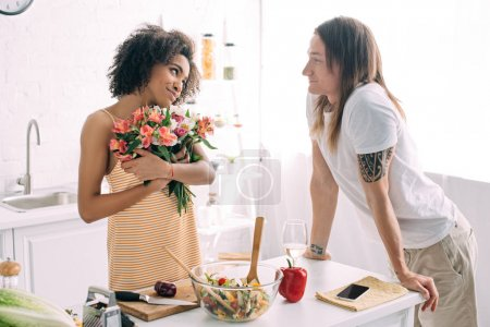 happy young african american woman holding bouquet of flowers and looking at boyfriend