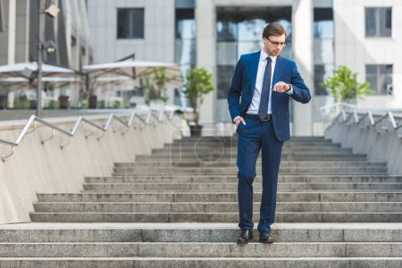 handsome young businessman in stylish suit standing on stairs near business building and looking at watch
