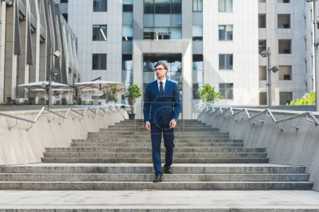 Photo for Handsome young businessman walking down stairs in business district - Royalty Free Image