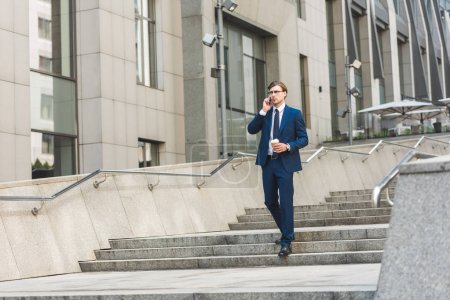 Photo for Businessman with coffee to go talking by phone while walking by stairs near business building - Royalty Free Image