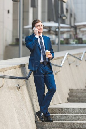 Photo for Successful young businessman in stylish suit with coffee to go talking by phone on stairs near business building - Royalty Free Image
