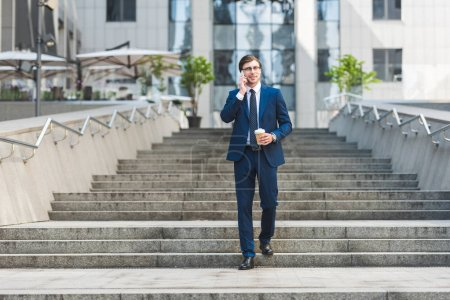 Photo for Smiling young businessman in stylish suit with coffee to go talking by phone while walking by stairs near business building - Royalty Free Image