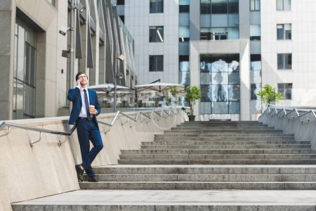 Photo for Handsome young businessman in stylish suit with coffee to go talking by phone on stairs near business building - Royalty Free Image