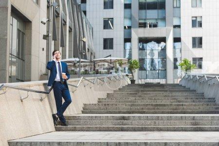 Photo pour Beau jeune homme d'affaires en costume élégant avec café pour aller parler par téléphone sur les escaliers près du bâtiment entreprise - image libre de droit