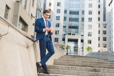 attractive young businessman in stylish suit with paper cup of coffee using smartphone on stairs near business building