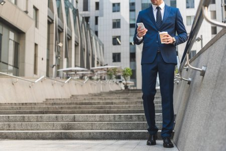 cropped shot of businessman in stylish suit with coffee to go using smartphone while going down stairs