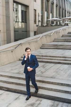 Photo for Handsome young businessman in stylish suit with coffee to go talking by phone while going down stairs - Royalty Free Image