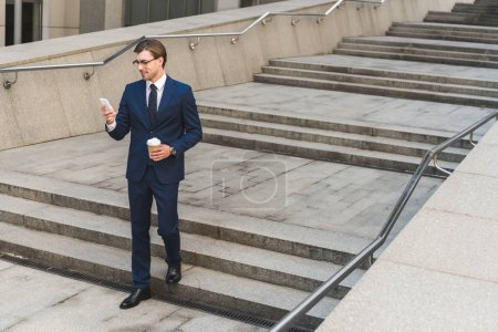 smiling young businessman in stylish suit with coffee to go using smartphone while going down stairs