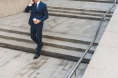 cropped shot of businessman in stylish suit with coffee to go talking by phone while going down stairs
