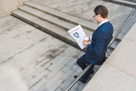 Photo for High angle view of young businessman with coffee to go reading newspaper - Royalty Free Image