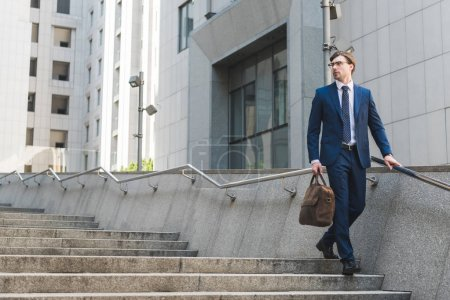 Photo for Attractive young businessman in stylish suit with briefcase in business district - Royalty Free Image