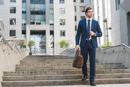 Photo for Handsome young businessman in stylish suit with briefcase in business district - Royalty Free Image