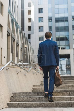 Photo for Rear view of businessman with leather briefcase going up stairs - Royalty Free Image