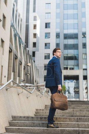 Photo pour Bel homme d'affaires en costume élégant avec serviette en cuir, monter des escaliers - image libre de droit