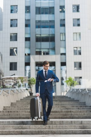 stylish young businessman with luggage and flight tickets walking by business district and looking at watch