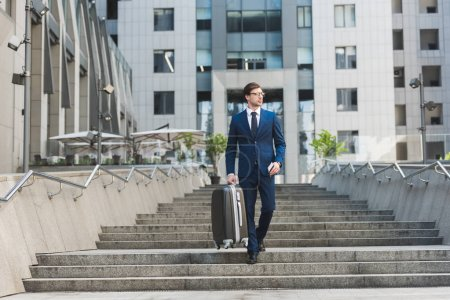 Photo for Young businessman in stylish suit with luggage and flight tickets going down stairs in business district - Royalty Free Image