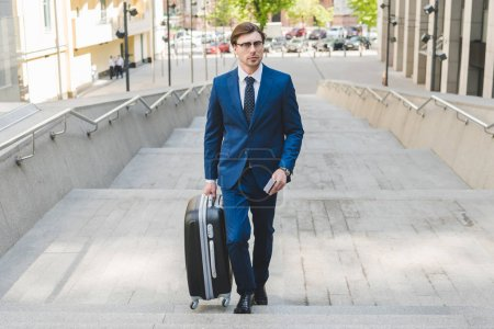 young businessman in stylish suit with luggage and flight tickets