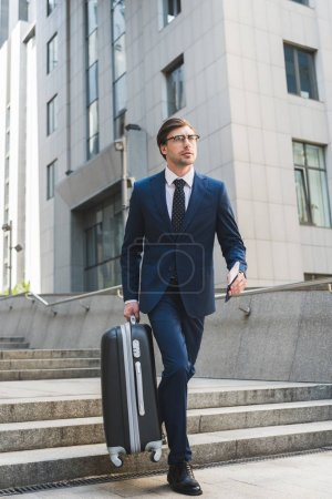 handsome young businessman in stylish suit with luggage and flight tickets going down stairs in business district