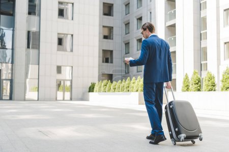 young businessman in stylish suit with luggage and flight tickets walking by business district
