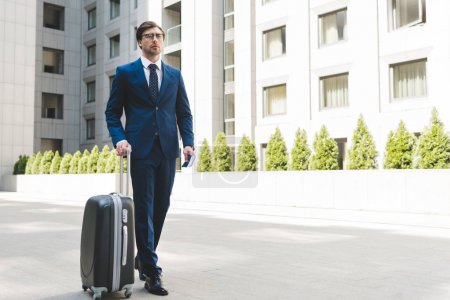 attractive young businessman in stylish suit with luggage walking by business district