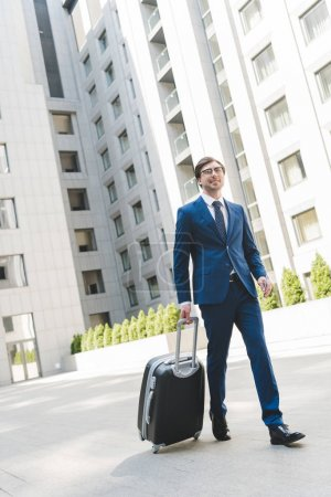 handsome young businessman in stylish suit with luggage walking by business district