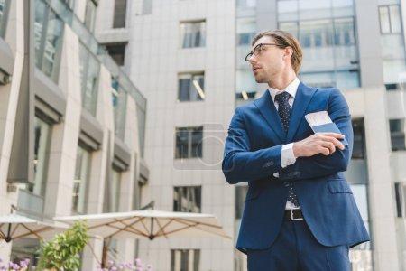 Photo pour Vue de dessous du gentil jeune homme d'affaires avec les bras croisés détenant des billets d'avion - image libre de droit