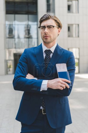 thoughtful young businessman with crossed arms holding flight tickets