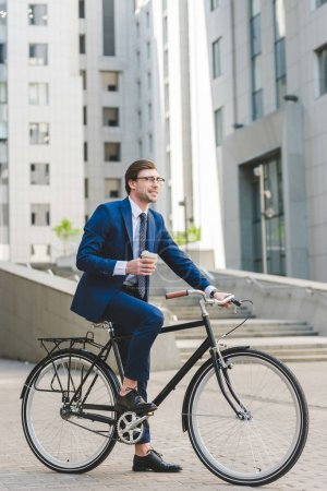 Photo for Handsome young businessman with paper cup of coffee on bicycle in business district - Royalty Free Image
