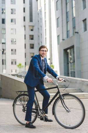 Photo for Handsome young businessman in stylish suit on bicycle in business district - Royalty Free Image