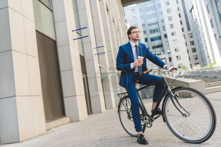 Photo for Handsome young businessman in stylish suit with coffee to go sitting on vintage bicycle - Royalty Free Image
