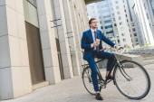 handsome young businessman in stylish suit with coffee to go sitting on vintage bicycle