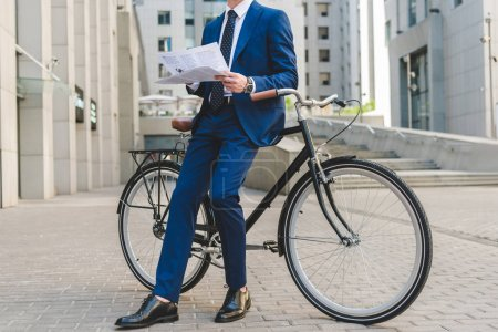 Photo for Cropped shot of businessman in stylish suit with newspaper leaning on bicycle - Royalty Free Image