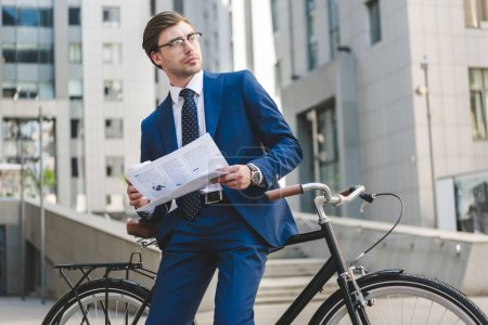 young businessman in stylish suit with newspaper leaning on bicycle