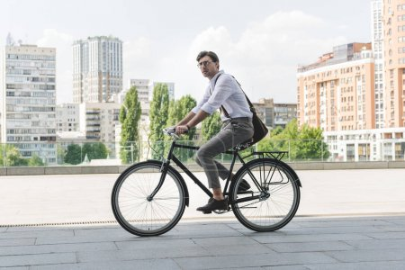 Photo for Side view of attractive young man in stylish clothes riding vintage bicycle on city street - Royalty Free Image