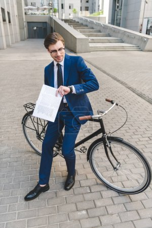 handsome young businessman in stylish suit with newspaper leaning on bicycle