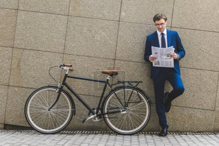 Photo for Handsome young businessman in stylish suit with bicycle reading newspaper leaning on wall - Royalty Free Image