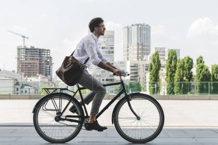 Photo for Side view of young man in stylish clothes riding vintage bicycle on city street - Royalty Free Image