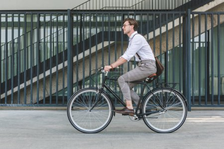 side view of handsome young man riding vintage bicycle on city street