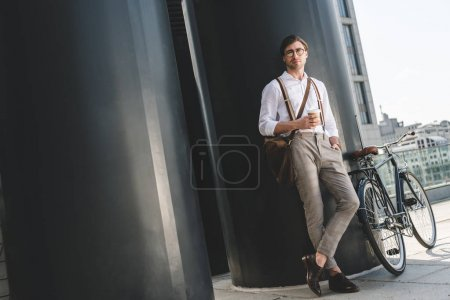 handsome young man with coffee to go and vintage bicycle on rooftop of business building