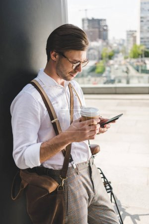stylish young man with paper cup of coffee to go using smartphone