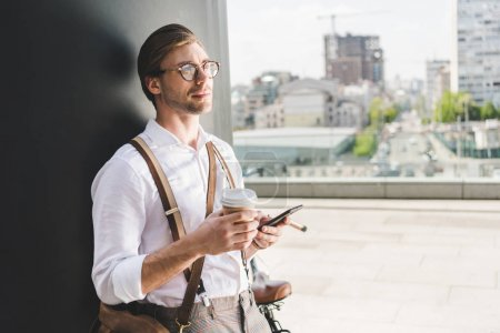 thoughtful young man with coffee to go using smartphone and looking away
