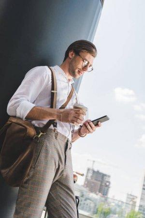 Photo pour Vue de dessous du beau jeune homme avec le café pour aller à l'aide de smartphone - image libre de droit