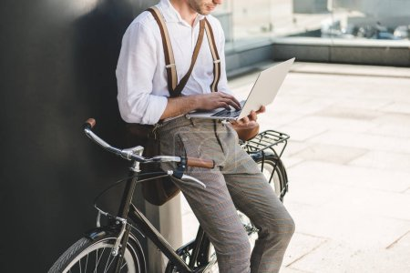 cropped shot of man working with laptop while leaning on vintage bicycle