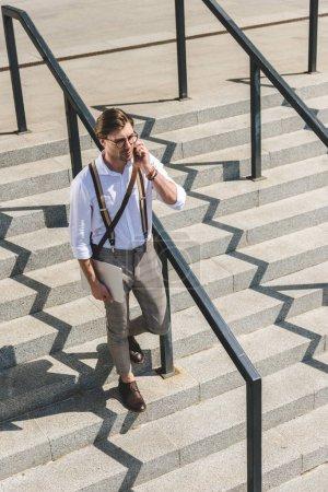 high angle view of stylish young man with folded laptop walking on stairs on city street and talking by phone
