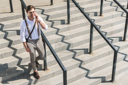 Photo for High angle view of handsome young man with folded laptop walking on stairs on city street and talking by phone - Royalty Free Image